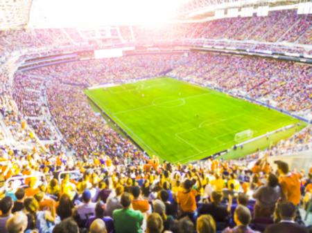 サッカー サッカー ファンは彼らのチームを応援し、明るい照明ビームとオープンエアで完全スタジアムでゴールを祝う-ぼやけています。