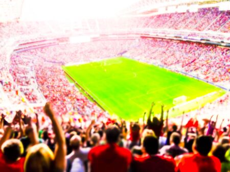 Football- soccer fans cheer their team and celebrate goal in full stadium with open air with bright lighting beam -blurred.
