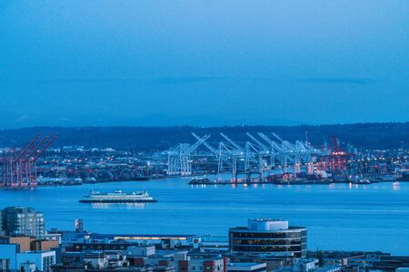 big ferry moving into downtown Seattle with industrail port background at night time,Seattle,Washington,usa.