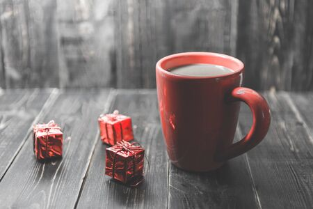 a red cup of coffee with red Christmas ornament on the dark wooden background.. Stock Photo