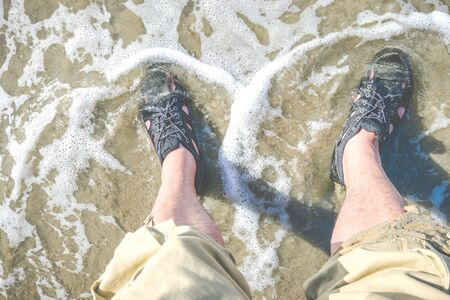 foot with water shoe on the beach. Banque d'images