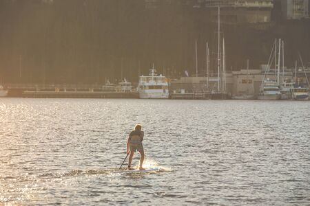 a man on paddle boarding on lake with yachts in background on sunset..