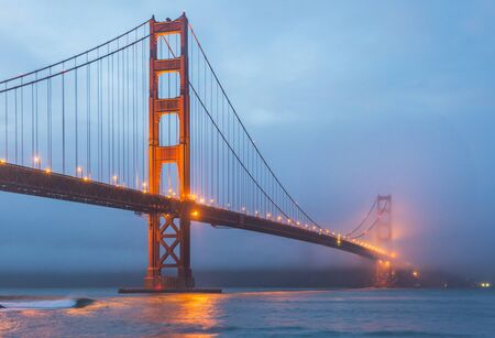 scenic view of Golden gate in the in the dusk with lighting and reflection on the water and fog,San Francisco,California,usa. Banco de Imagens