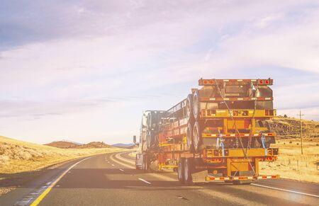 truck driving on the asphalt road in rural landscape at sunset Stok Fotoğraf
