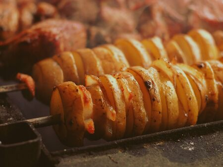 Grilling sliced potatoes and bacon shashlik skewers on barbecue