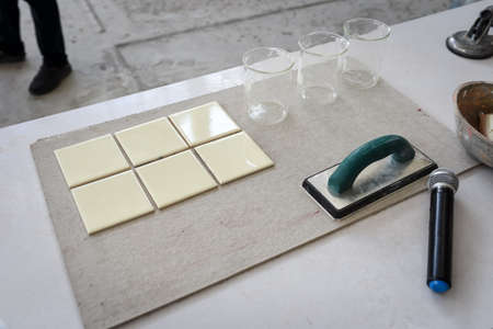 demonstration how to grout tile with tile grout on the table