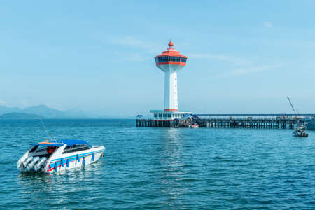 Speed boat and white and orange lighthouse at blue sea for tour travel.