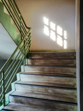 Old design staircase with a dirty and sun shine througe window