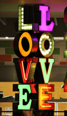 the word LOVE written in Neon lights with bright varied colours photo