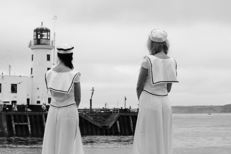 sailor girls in uniform looking out to sea photo