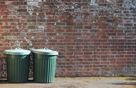 old trashcan dustbins against brick wall