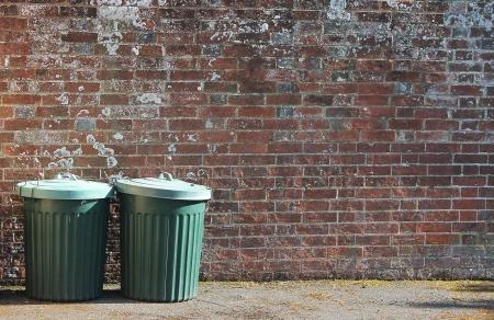 trashcan: old trashcan dustbins against brick wall