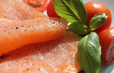 Rose coloured smoked salmon on toast, basil and tomatoes photo