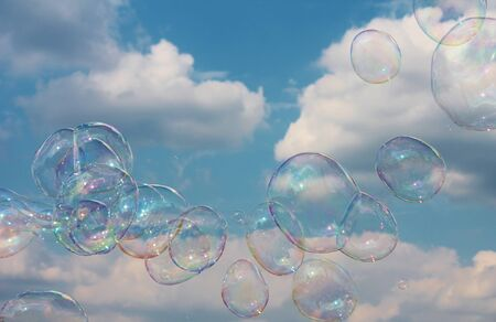Dreamy Soap Bubbles floating on the breeze in the blue and cloudy sky photo
