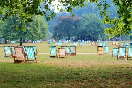Striped deck chairs in park on grass - Stock Photo