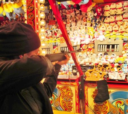 bb gun: woman shooting at target gallery game at funfair Editorial