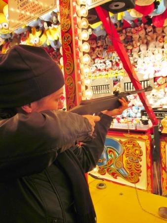 bb gun: woman shooting game at target gallery at funfair with gun Editorial