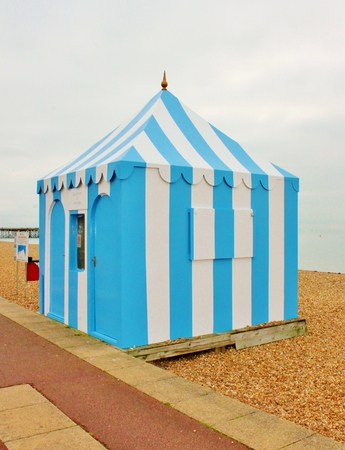 Vintage retro striped beach tent marquee on shingle pebbles at  photo