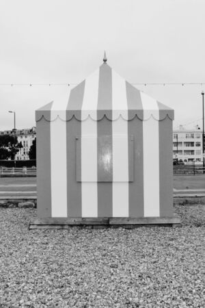 Vintage retro striped beach tent marquee on shingle pebbles  photo