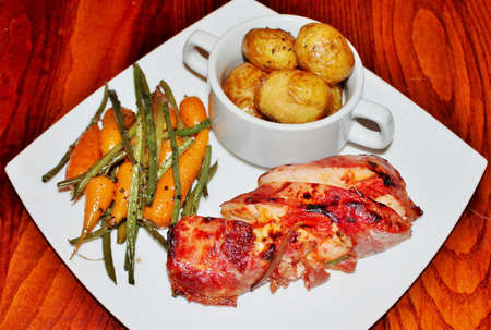 Chicken wrapped ham, new potatoes and vegetables  photo