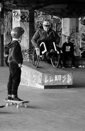 raising cans: Man in a wheelchair doing stunts on ramp child watches Editorial