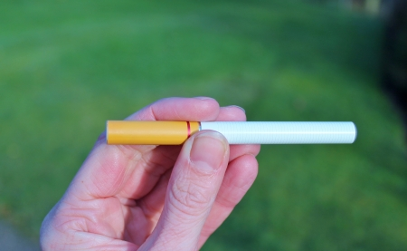 background e cigarette: Electronic cigarette battery powered vapour ecigarettes against grass Stock Photo