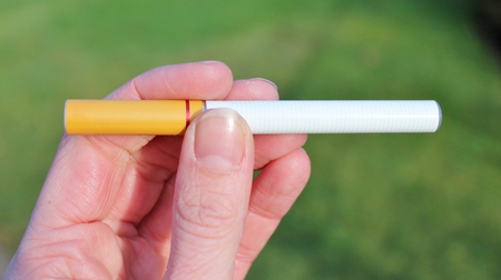 e cigarette: electronic battery powered vapour e-cigarettes against green grass Stock Photo