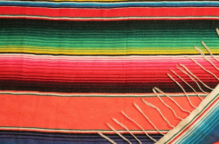 Traditional Mexican fiesta poncho rug in bright colors background