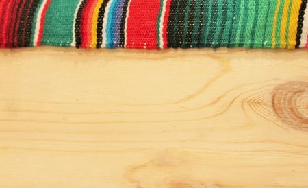 wooden background with serape poncho edge stripe
