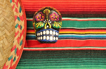Traditional Mexican fiesta poncho rug in bright colors with a mask Stock Photo