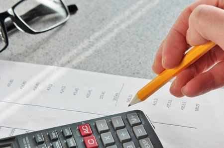 calculating tax maths Bank statement with pencil and calculator photo