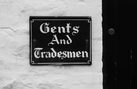 door swings: old pub sign Gents and tradesmen entrance  Stock Photo