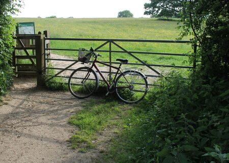 coutryside: Old bicycle with basket leaning against field gate in country