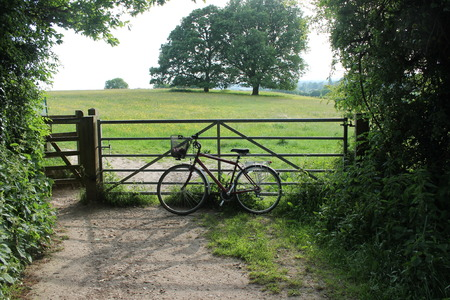 Old bicycle with basket leaning against field gate in country  photo