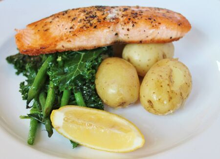 Balanced meal Grilled pan seared Scottish salmon with new potatoes, seasonal greens lemon wedge  photo
