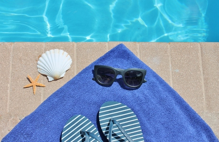 Swimming pool shoes thongs flip flops towel and shell starfish photo