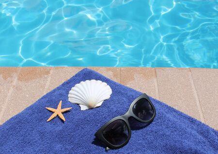 Swimming pool sunglasses towel and shell starfish photo
