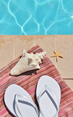sandels: Swimming pool towel shoes starfish and shell Stock Photo