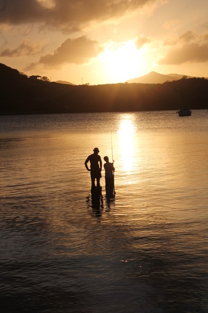 father and son family fishing at sunset photo