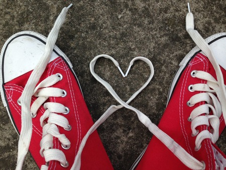 teen feet: baseball boots sneakers with love heart Stock Photo