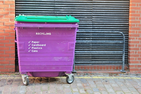 Dustbins outside against brick wall photo