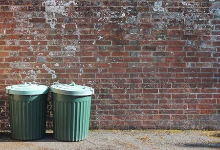 brick background: dustbins outside against brick wall