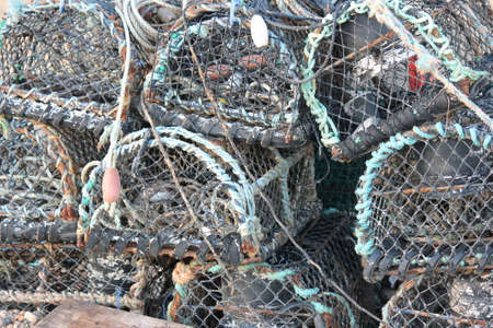lobster pot: Fishing boat on pebble beach shore with lobster pot traps