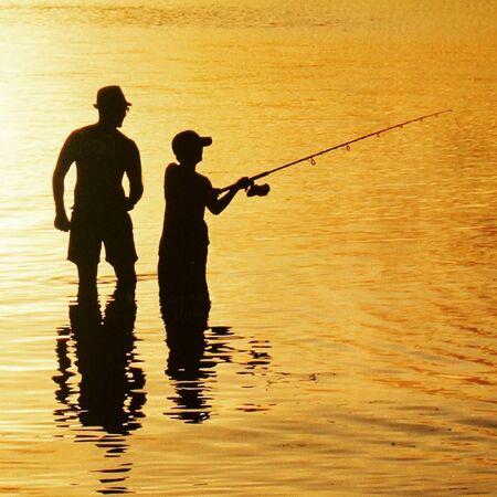 cast off: father son fishing sunset in water cast off Stock Photo