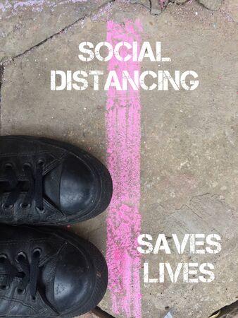 social distancing coronavirus concept tape feet floor - social distance to slow/stop the spread of the virus Фото со стока