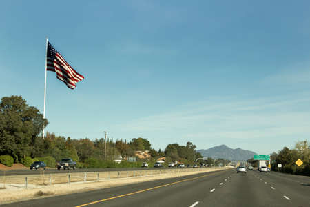 interstate: A large US flag waves at passers- by on interstate 5 near Anderson, California.