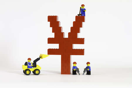 A red Chinese Yuan symbol constructed from toy bricks by model figures and shot against a white background at an angle to show its 3D nature.  Growth of the Chinese economy. photo