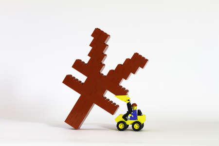 A red Yuan symbol constructed from toy bricks and shot against a white background at an angle to show its 3D nature.  Model figures are supporting a falling Yuan suggesting a financial issue. photo