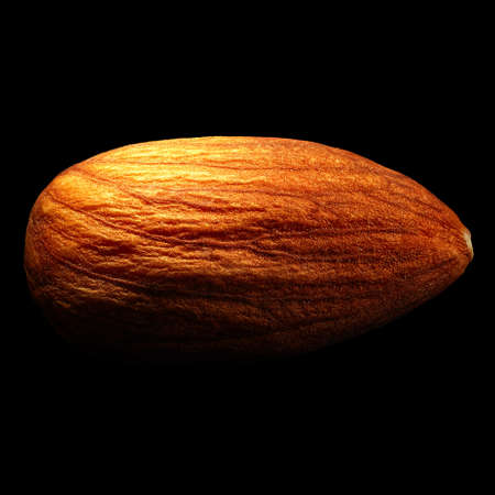 Almond isolated on black background with reflection. Close-up or macro. Health concept
