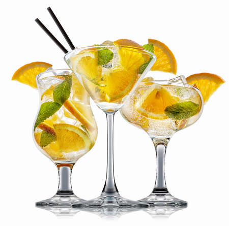 fresh fruit alcohol cocktail or mocktail in classic glass with ice cubes, orange and mint isolated on white background